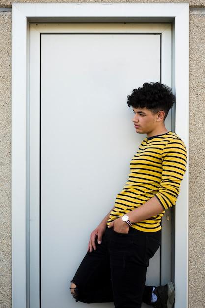 Homem latino-americano encaracolado novo que inclina-se na embalagem da porta Foto gratuita