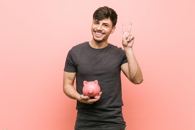Homem latino-americano novo que guarda o mealheiro que mostra o sinal da vitória e que sorri amplamente. Foto Premium