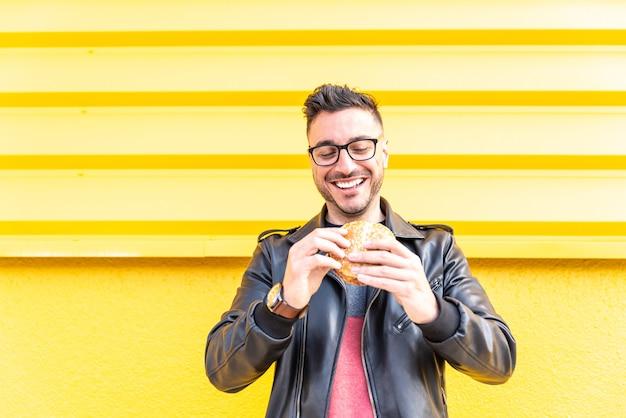 Homem latino comendo um hambúrguer ao ar livre Foto Premium