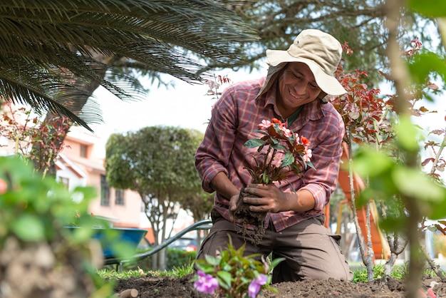 Homem latino plantando flores em um belo jardim verde Foto Premium