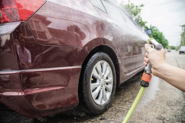 Homem, lavando, carro, usando, shampoo, e, água Foto gratuita