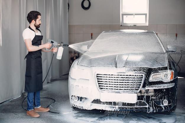 Homem lavando o carro em uma garagem Foto gratuita