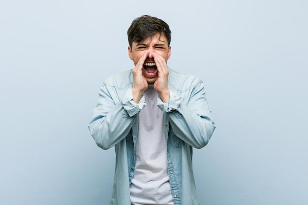 Homem legal hispânico jovem gritando animado para a frente. Foto Premium