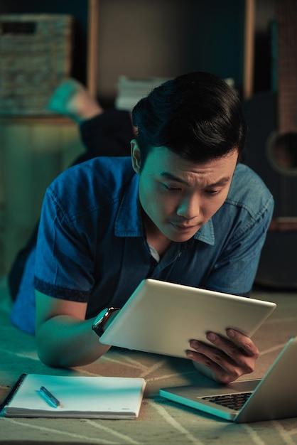 Homem lendo algo sobre o tablet Foto gratuita