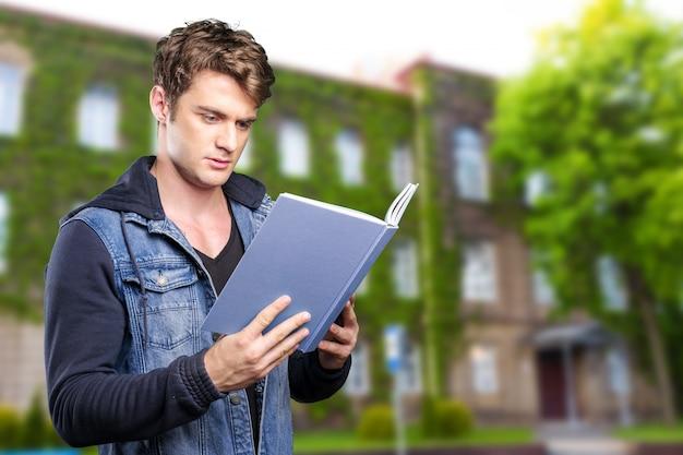 Homem lendo livro nas mãos Foto Premium