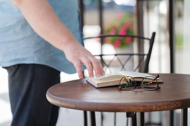 Homem lendo um livro com beber café ou chá Foto Premium