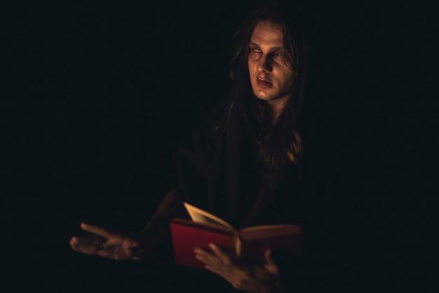 Homem lendo um livro de feitiços vermelho no escuro e olhando para longe Foto gratuita