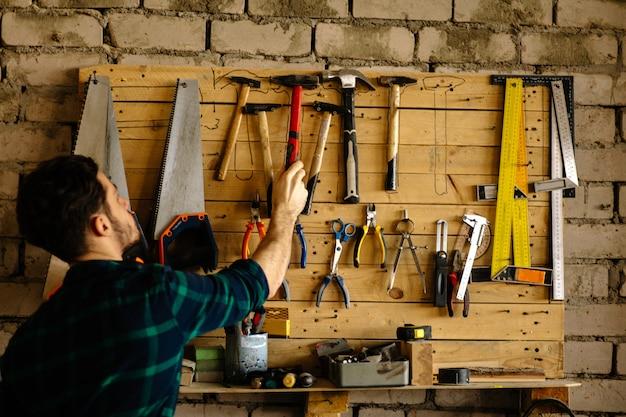 Homem leva martelo de parede com ferramentas Foto Premium
