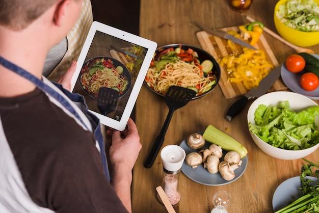 Homem, levando, foto, de, prato preparado Foto gratuita