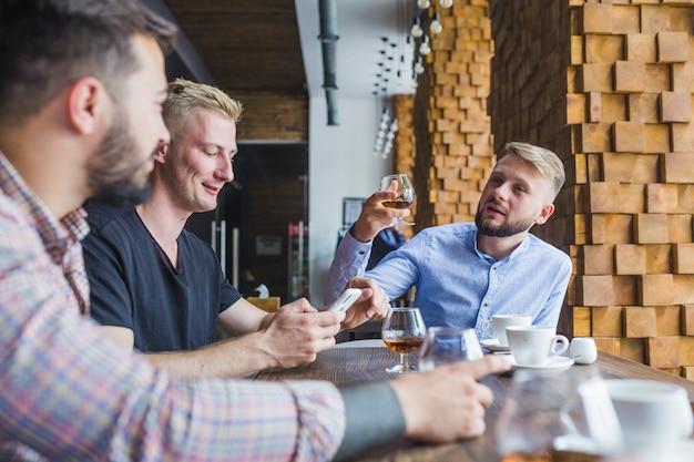 Homem levantando brinde com seus amigos no restaurante Foto gratuita