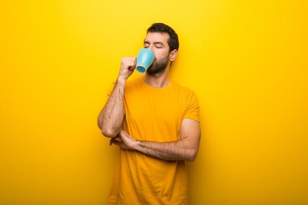 Homem, ligado, isolado, vibrante, cor amarela, levando, um, café, em, takeaway, copo papel, e, sorrindo Foto Premium
