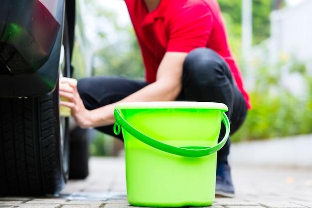 Homem limpando a jante da roda durante a lavagem do carro Foto Premium