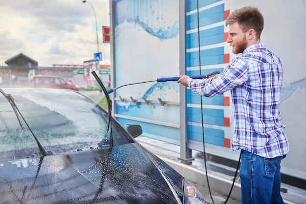 Homem limpando o carro em um self-service Foto gratuita