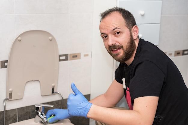 Homem, limpeza de vaso sanitário. emoção positiva mostrando os polegares para cima. Foto Premium