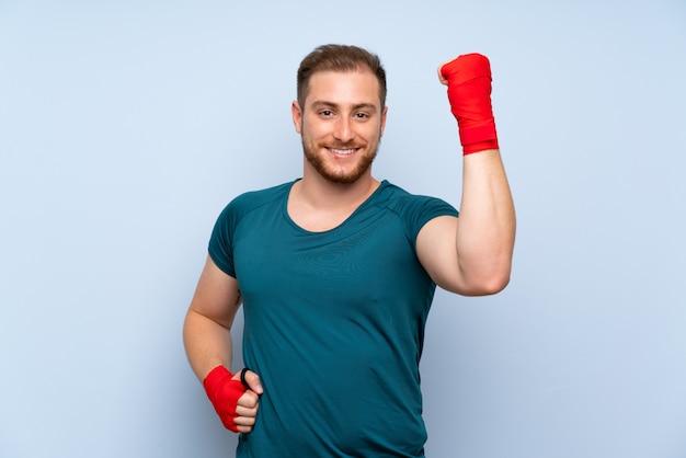 Homem loiro esporte parede azul em bandagens de boxe Foto Premium