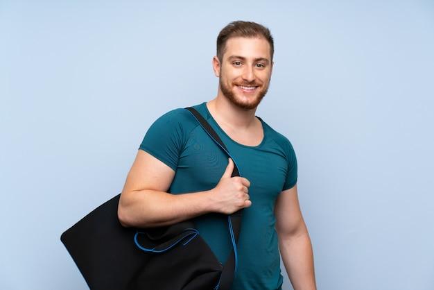 Homem loiro esporte parede azul sorrindo muito Foto Premium