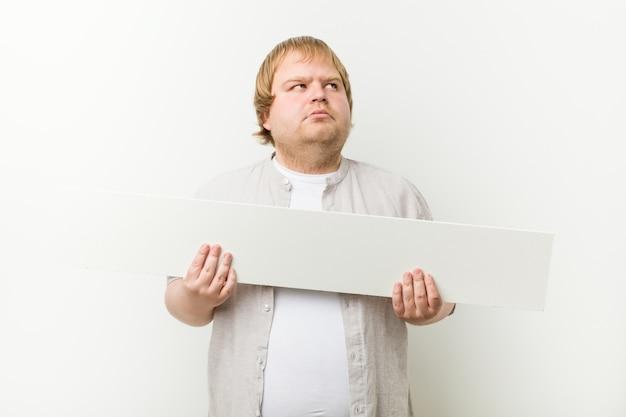 Homem loiro louco caucasiano com um cartaz Foto Premium
