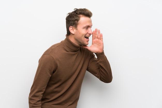 Homem loiro sobre parede branca isolada gritando com a boca aberta para o lateral Foto Premium