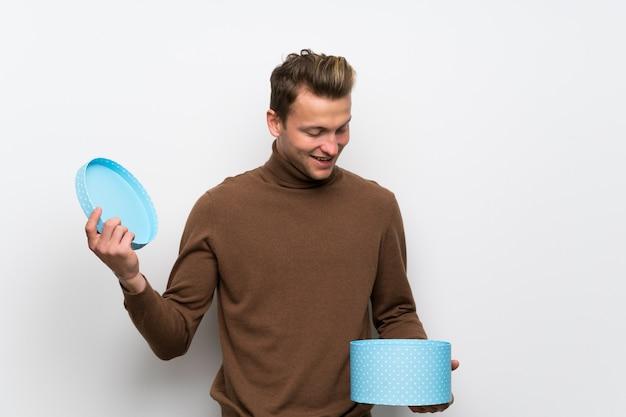 Homem loiro sobre parede branca isolada, segurando um presente nas mãos Foto Premium