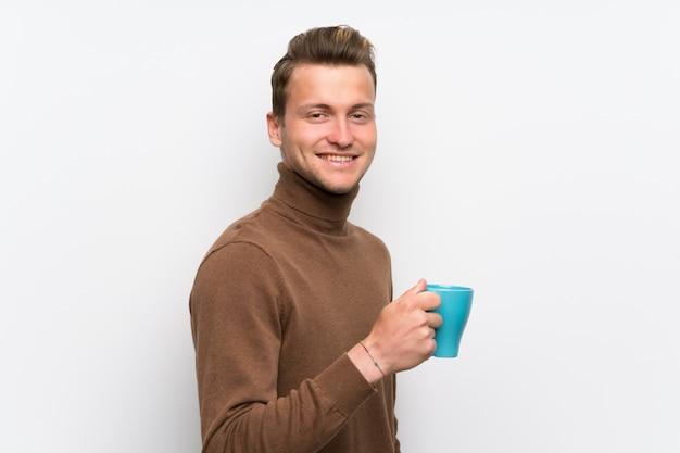Homem loiro sobre parede branca isolada, segurando uma xícara de café quente Foto Premium