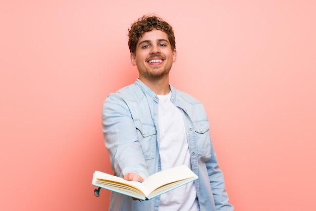 Homem loiro sobre parede rosa segurando um livro e dando a alguém Foto Premium