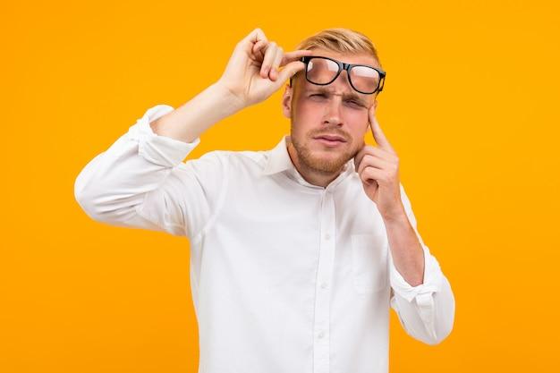Homem loiro vestido com uma camisa branca clássica estrabismo ao tirar os óculos no amarelo Foto Premium
