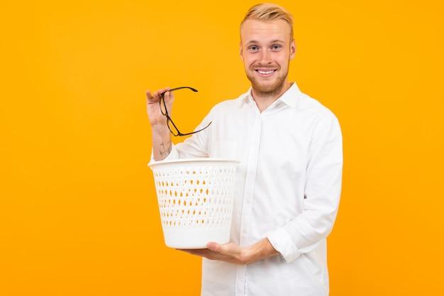 Homem loiro, vestido com uma camisa branca clássica lança óculos na lixeira onyellow Foto Premium
