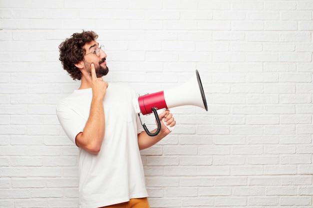 Homem louco novo com um megafone contra a parede de tijolo. Foto Premium
