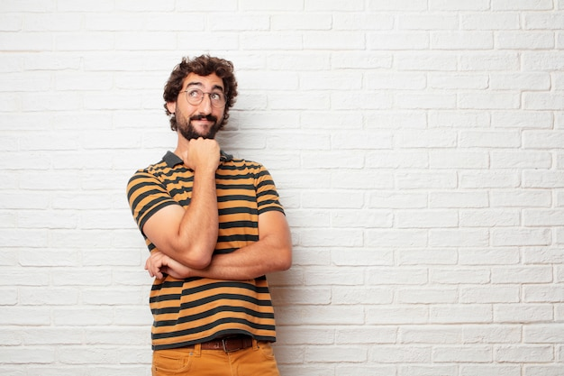 Homem louco ou bobo jovem gesticulando e expressando emoções contra o fundo da parede de tijolo Foto Premium