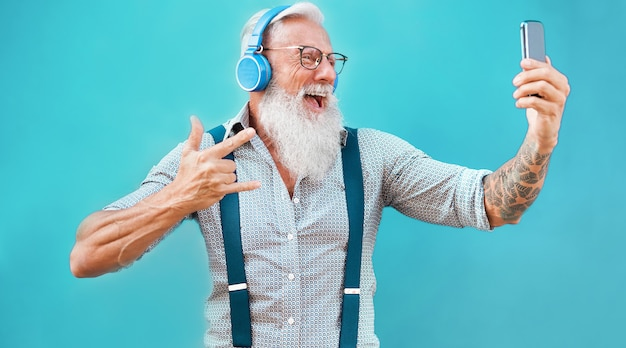 Homem louco sênior usando o aplicativo de smartphone para criar lista de reprodução com música rock - cara de tatuagem na moda se divertindo com a tecnologia do telefone móvel - tecnologia e conceito de estilo de vida alegre e idoso - foco no rosto Foto Premium