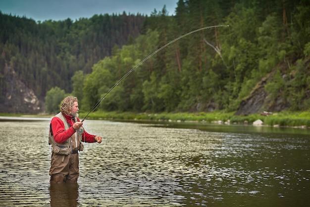 Homem maduro barbudo branco molhado está parado na água no meio do rio e pesca pesca com mosca, turismo ecológico. Foto Premium