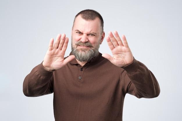 Homem maduro com barba mostra gesto de recusa, não quer falar com você Foto Premium