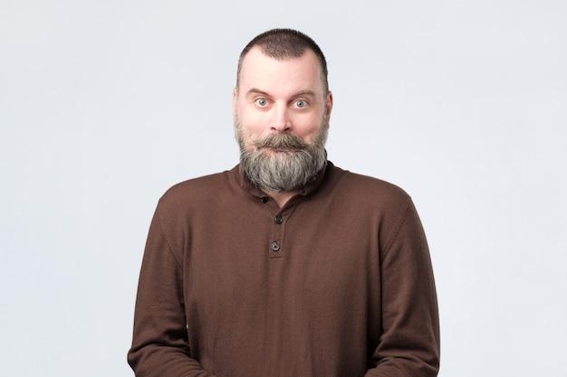 Homem maduro com cara de espanto como se estivesse chocado com a notícia Foto Premium