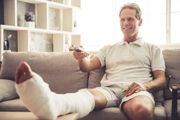 Homem maduro considerável com pé quebrado na gipsita. Foto Premium