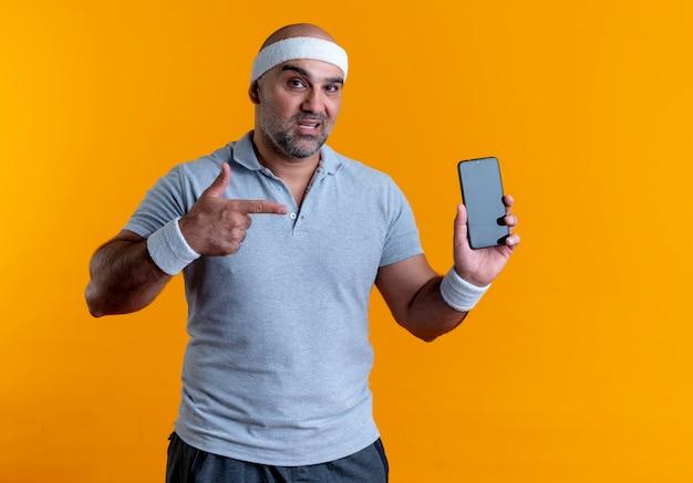 Homem maduro e desportivo com uma bandana mostrando o smartphone apontando com o dedo para ele, parecendo confiante em pé sobre a parede laranja Foto gratuita