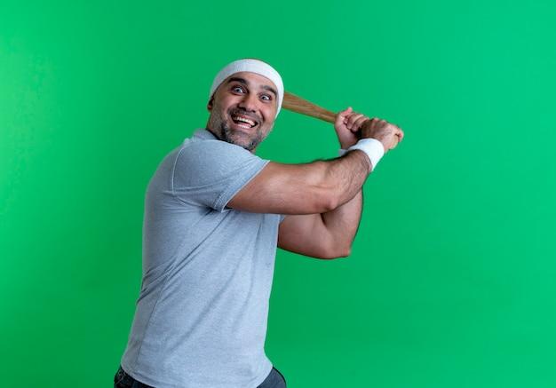 Homem maduro e esportivo com uma faixa na cabeça balançando um taco de beisebol e sorrindo alegremente em pé sobre a parede verde Foto gratuita