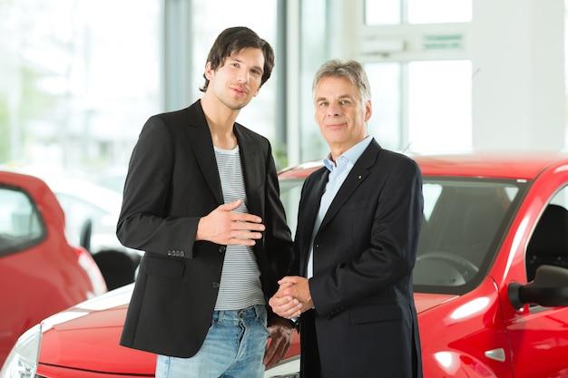 Homem maduro e jovem com automóveis na concessionária Foto Premium