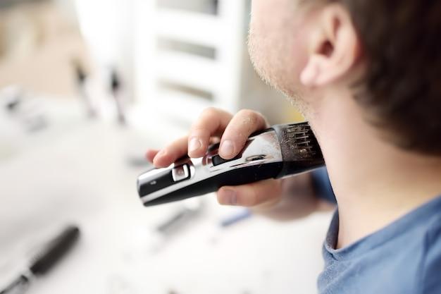 Homem maduro está raspando a barba com um barbeador elétrico em casa Foto Premium