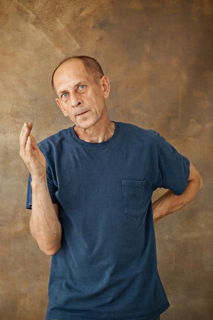 Homem maduro preocupado em pé no estúdio Foto gratuita