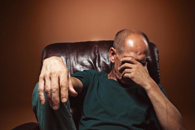 Homem maduro preocupado sentado Foto gratuita