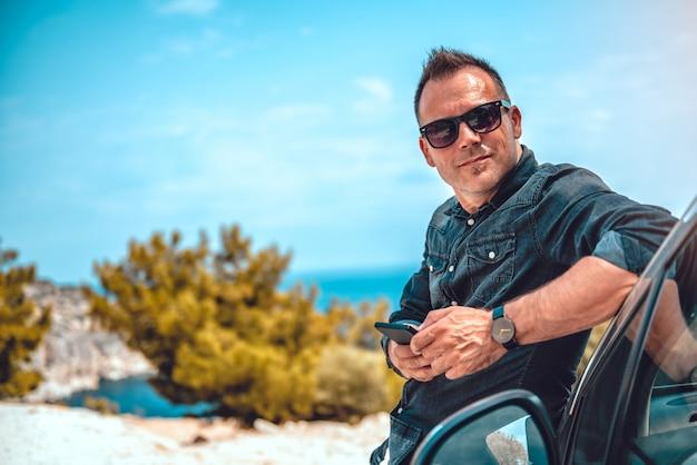 Homem magra no carro usando telefone inteligente Foto Premium