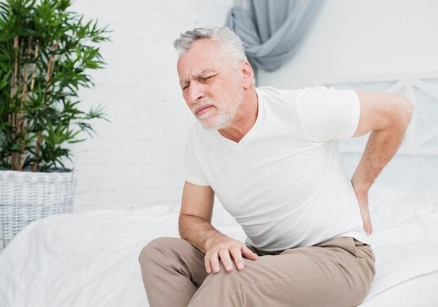 Homem mais velho com dor nas costas Foto gratuita