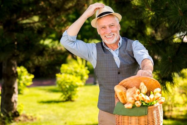 Homem mais velho com uma cesta ao ar livre Foto gratuita