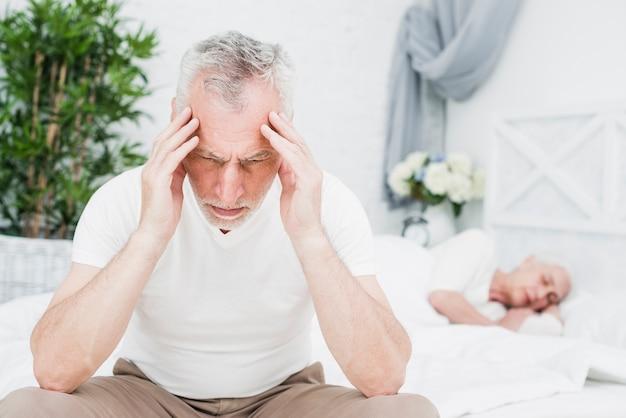 Homem mais velho com uma dor de cabeça Foto gratuita