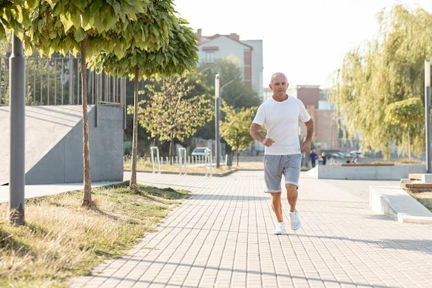 Homem mais velho correndo na calçada Foto gratuita