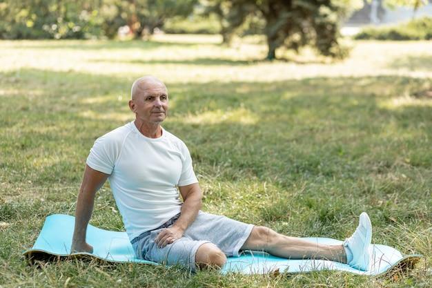 Homem mais velho, estendendo-se no tapete de ioga na natureza Foto gratuita