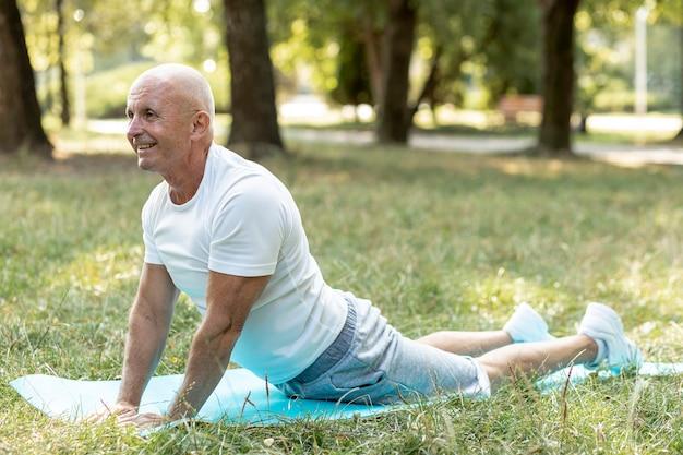 Homem mais velho feliz praticando ioga fora Foto gratuita
