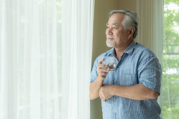 Homem mais velho se sentir feliz bebendo água fresca de manhã, aproveitando o tempo em sua casa Foto Premium