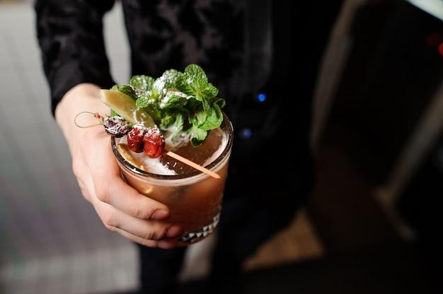Homem mantém coquetel alcoólico com um raminho de hortelã-pimenta, cereja e açúcar em pó Foto Premium