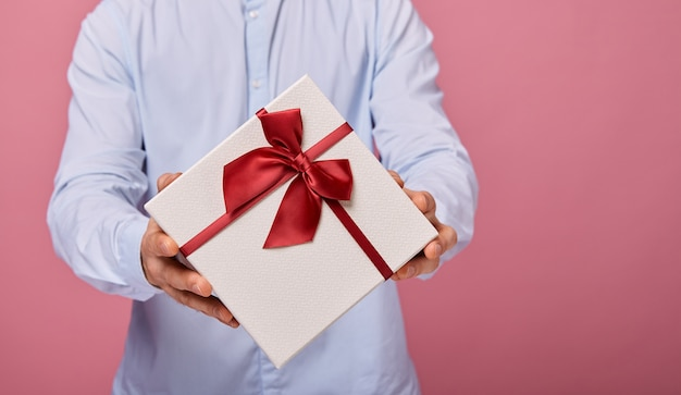 Homem mantém presente em caixa branca com tampa azul e laço branco Foto Premium